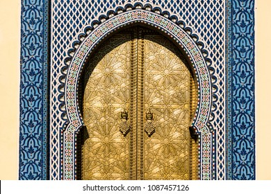 Brass gate and zellige mosaic floral tilework on doorway of traditional Moroccan building