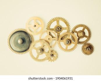 Brass gear cogs set. Wheel symbol, machine engine element. Isolated elements cream background.
