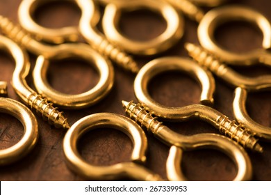 Brass hook or ring aligned, on a rustic wooden surface. Extremely shallow depth of field.