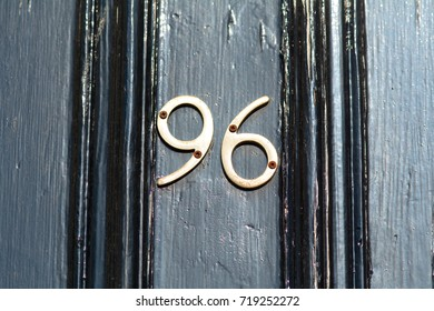 Brass house number 96 sign on door