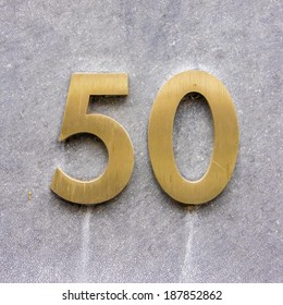 Brass house number fifty on a stone wall