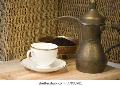Brass Jordanian coffee pot with a teacup and ground coffee.