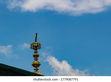 Brass Kalash on top of Gurudwara with blue sky and clouds in background.