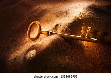 Brass key laying in sand