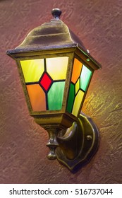 Brass lamp on the wall. Night lamp with color glass. Metal lantern.