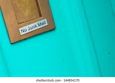 Brass letterbox on a colorful turquoise blue door bearing the sign No Junk Mail