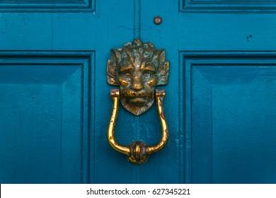 Brass lion head knocker, knocker on blue wooden door, decorative element, vintage