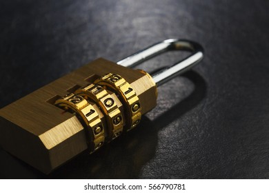 Brass lock with the code set on the dark surface