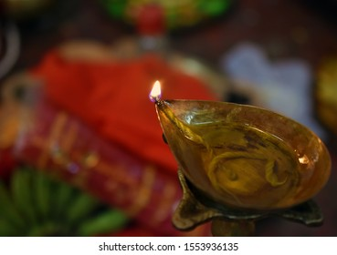 Brass made oil lamp (diya) Burning in puja with blur background