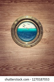 Brass porthole at the old sailing vessel for your vertical poster in marine style with place for text. Porthole window on the yacht with view on ocean and flying sea birds over the coral reefs.