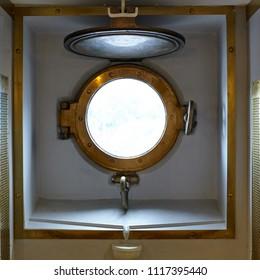 Brass porthole on an old military steam ship of the late 19th century.
