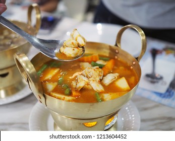 A brass pot of hot and sour yellow curry paste soup with crab and mixed vegetable such as coconut shoot, carrot and long bean. Thai traditional food with selective focus.