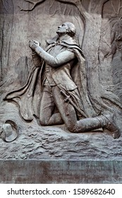 Brass relief of George Washington kneeling in prayer at Federal Hall in New York City. United States.June 2013.