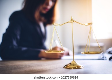 Brass scale of judge on lawyer desk with lawyer sitting working in background for signing important documents. lawyer and law ,judiciary and legislature courtroom legal concept.