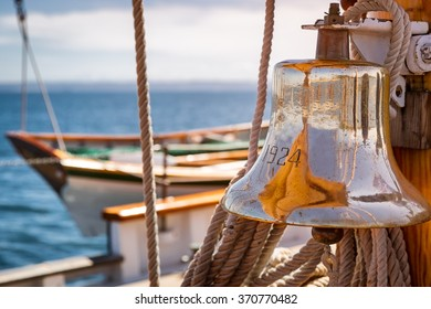 Brass ship bell on a classic sailboat at sea. Close up of the shiny bell reflecting the sails.