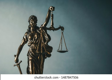 Brass statue of a blindfolded Justice holding scales and sword over a graduated grey background and copy space in a conceptual image
