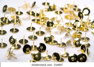Brass thumb tacks scattered against a white background.