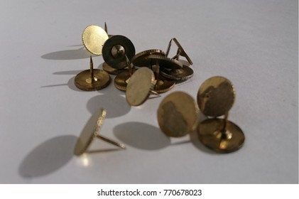 Brass thumb tacks. These are brass thumb tacks taken on  white paper background using natural lighting.