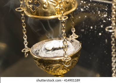 Brass thurible liturgy censer with coal, ash, smoke and incense in it. Christian Church accessory. Closeup. Selective focus.