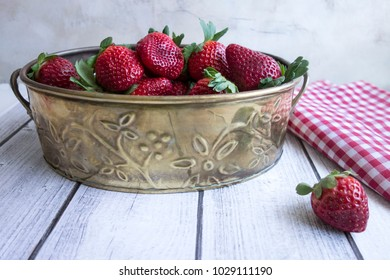 A brass tin filled with strawberries on a wood surface with a red and white gingham napkin.