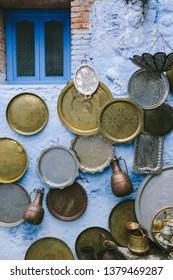 Brass trays, a typical handmade product from Morocco, on display on a blue painted wall in Chefchaouen, Morocco.