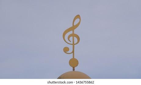 Brass treble clef building ornament