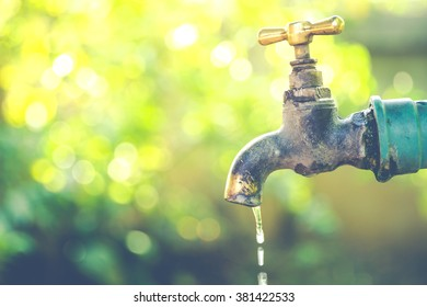 Brass water tap in nature background.(Processed in vintage colour tone)