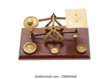 Brass and wood scales and small weights in ounces on a white background, with 'made in England' stamped on the scales