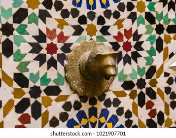 A brass-colored bear-shaped spigot on a tiled wall in the old town of Tangier Morocco.