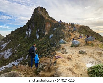 Brastagi, Medan, Indonesia - 2019/07/14 - Dad with his son hiking Sibayak Mountain after Sunrise.