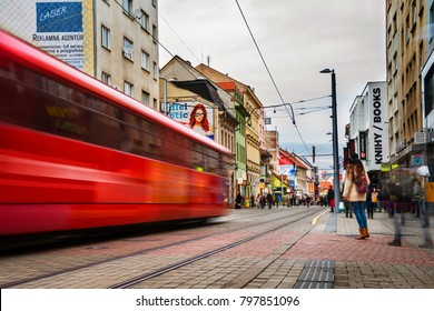 BRATISLAVA, SLOVAK REPUBLIC - FEBRUARY 8, 2016: Blurred tram in the center of Bratislava, Slovakia in the evening. Famous old buildings and people