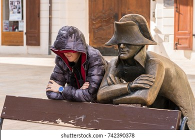 Bratislava, Slovak Republic - October 9, 2017: Life imitating art as young man leans against town center park bench next to Napoleonic statue in Bratislava.