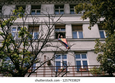 Bratislava, Slovakia, 07/2018. Queer parade. Woman with a rainbow flag supporting the parade, waving at the crowd marching the streets from her window in a tall residential building.