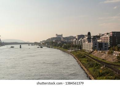 Bratislava, Slovakia - 10/10/2014 - Panorama photo of Bratislava city with business centre on riverside with SNP bridge and Bratislava Castle in distance.