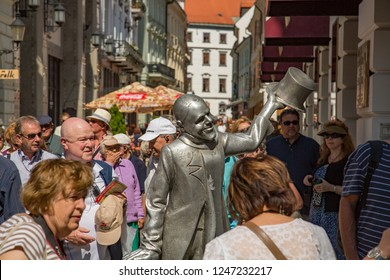 Bratislava, Slovakia - 7/11/2013:  Crowded sidewalk with statue of silver man with top hat.  Some of the most photographed attractions of Bratislava are its sculptures in human size