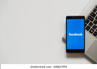 Bratislava, Slovakia, April 28, 2017: Facebook logo on smartphone screen placed on laptop keyboard. Empty place to write information.
