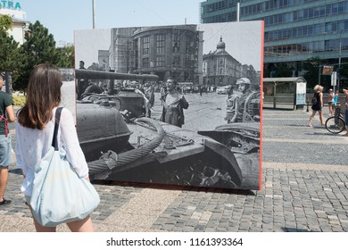 BRATISLAVA, SLOVAKIA - AUGUST 21, 2018:  young lady looks at iconic photograph of L. Bielik: The Bare-chested Man in Front of the Occupiers Tank at Hodzovo square in Bratislava, Slovakia