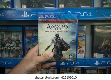 Bratislava, Slovakia, circa april 2017: Man holding Assassin's Creed Ezio Collection videogame on Sony Playstation 4 console in store