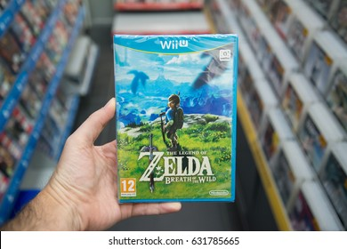 Bratislava, Slovakia, circa april 2017: Man holding The Legend of Zelda: Breath of the Wild videogame on Nintendo WiiU console in store