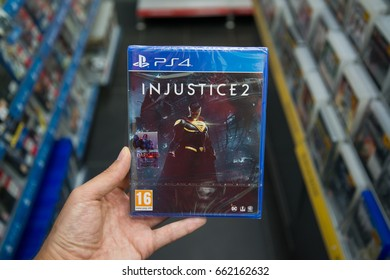 Bratislava, Slovakia, june 15, 2017: Man holding Injustice 2 videogame on Playstation 4 console in store