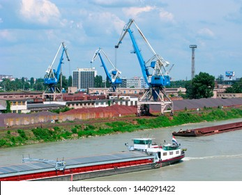 Bratislava, Slovakia - June 24, 2019: Cargo port on the Danube. Cranes load coal coke in railway cars. Mountains of bulk cargo: iron ore and coal coke. A bulk cargo ship and a barge on the river.