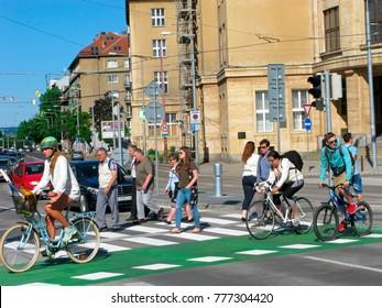 Bratislava, Slovakia - June 8, 2017: People on pedestrian crossing. Pedestrians walking along white strips of crosswalk, bicyclists biking on special green lane.