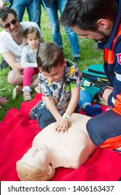 BRATISLAVA, SLOVAKIA - MAY 18, 2019: Male rescuer demonstrating CPR to kids with an emergency dummy