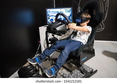 BRATISLAVA, SLOVAKIA - OCT 25, 2019: Young boy plying racing game on 2DOF motion simulator with virtual reality glasses at the mall in Bratislava, Slovakia