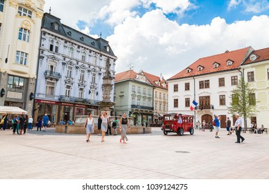 BRATISLAVA, SLOVAKIA - SEPTEMBER 17, 2016 : Historical sqaure of Bratislava and tourists travel by red bus. City is touristic, political and cultural center of Slovakia.