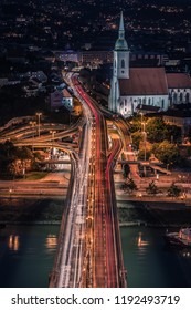 BRATISLAVA, SLOWAKIA - SEPTEMBER 20, 2018: The capital Bratislava of Slowakia during the evening blue hour by night, with a view of the church and the bridge crossing the Danube river