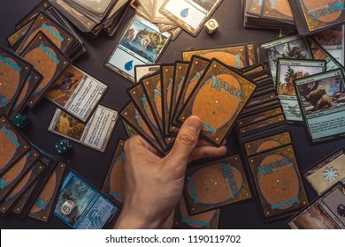 Bratislava/Slovakia - 06/13/2018: Magic the Gathering card playing game background with hand holding cards and cards and dice spread out behind