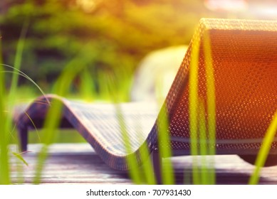 braun beach chair over green nature background, sunny summer outdoor day light, summer holiday concept