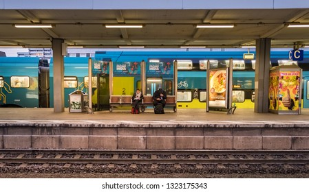 Braunschweig, Germany - December 12, 2018 : Passengers sitting on wooden bench at Braunschweig Hauptbahnhof station.