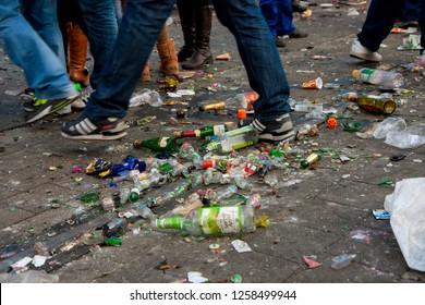 Braunschweig, Germany - March 06, 2011: Legs and feet of people walking through heavily polluted street because of thrown away empty bottles after a carnival parade